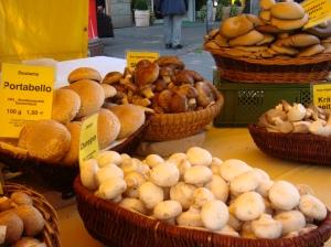 Feira em Frankfurt, na Alemanha, em 2009. Vários cogumelos diferentes. A moça da banca ficou impressionada com a minha surpresa de ver tantos fungos ali reunidos, todos frecos (= Aí ela me ofereceu um e eu comi